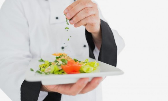 male-chef-garnishing-fresh-prepared-meal