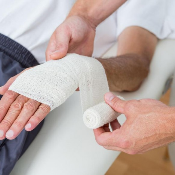 doctor-bandaging-his-patient-hand